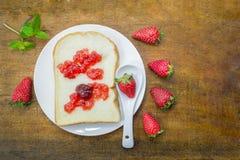 Skiva för vitt bröd med jordgubbedriftstopp Arkivbild