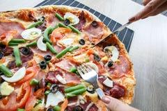 Skiva ny pizza med peperonin och grönsaker Royaltyfria Bilder