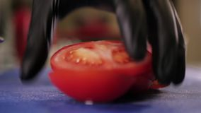 Skiva tomaten med k?kkniven arkivfilmer