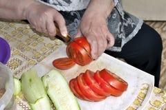 Skiva tomater och zucchinin på skärbrädan Royaltyfria Foton