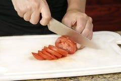 skiva tomatoe för kniv Arkivfoto