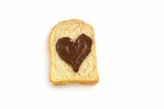 Skivabröd med hjärtaform av den bästa sikten för chokladhasselnötspridning Arkivbild