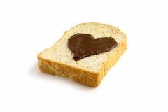 Skivabröd med hjärtaform av sikten för sida för chokladhasselnötspridning Royaltyfri Fotografi