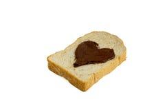 Skivabröd med hjärtaform av sikten för sida för chokladhasselnötspridning Arkivfoto