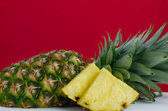 Skivad ananasfrukt på röd bakgrund Royaltyfria Bilder