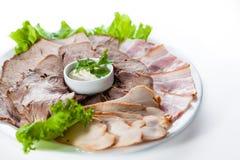 Skivad bacon och skinka med grönsallat på den vita plattan Arkivbild