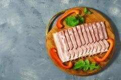 Skivad bacon på en skärbräda, grå bakgrund Bästa sikt, kopieringsutrymme royaltyfri fotografi