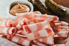 Skivad bacon tjänade som med sås och gravade gurkor på plattan Royaltyfri Fotografi