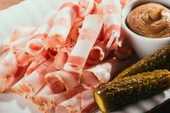 Skivad bacon tjänade som med sås och gravade gurkor på plattan Royaltyfria Bilder