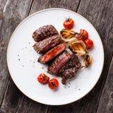 Skivad biff Ribeye med lökar och tomater Arkivfoto