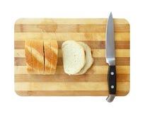 Skivad bröd och kökkniv på skärbräda Royaltyfria Foton