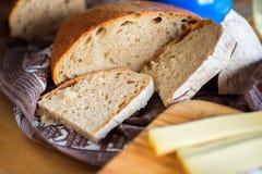 Skivad bröd och ost på träkökbräde Fotografering för Bildbyråer