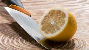 Skivad citron med kniven Fotografering för Bildbyråer