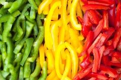 Skivad färgglad paprika pepprar bakgrund Arkivfoto