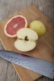 Skivad frukt på träyttersida med kniven Royaltyfri Bild
