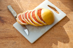 Skivad grapefrukt med kniven Arkivfoton