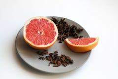Skivad grapefrukt- och stjärnaanisart på plattan royaltyfri foto