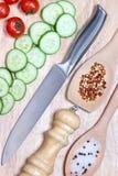 Skivad gurka, körsbärsröda tomater, krydda på träskärbräda sund begreppsmat Arkivfoton