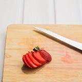 Skivad jordgubbe på träskärbräda för naturlig färg Arkivfoto