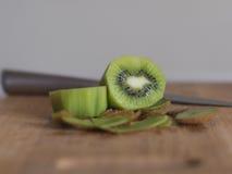 Skivad kiwi med kniven på träbräde arkivfoton