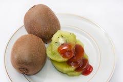 Skivad kiwi och överträffat med jordgubbesirap Arkivfoton