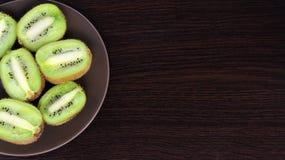 Skivad kiwi på en platta, på en mörk bakgrund royaltyfri fotografi