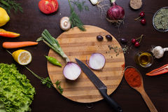Skivad lök på skärbrädan, variationsgrönsaker och kryddor omkring Royaltyfria Foton