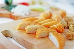 Skivad laksa för fiskkaka på träskärbräda i kök Royaltyfria Bilder