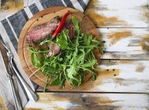 Skivad medelsällsynt grillad nötköttbiff Ribeye med nolla för raketsallad Fotografering för Bildbyråer