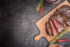 Skivad medelsällsynt grillad biff på lantlig skärbräda med rosmarin och kryddor Arkivfoto