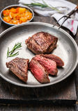 Skivad medelsällsynt grillad nötköttbiff, filetmignon, i lantlig platta för metall med köttgaffeln och salsasås på mörk träbackgr Arkivfoto