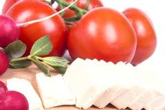 Skivad ost på tabellen med nya grönsaker Royaltyfri Fotografi