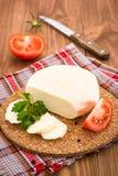 Skivad ost, tomat och persilja på en substrate på en trätabell Arkivfoto