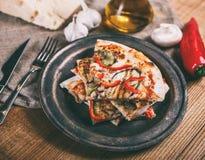 Skivad pizza med höna, zucchinin, aubergine, peppar, ost och champinjoner på plattatappningen arkivfoton