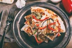Skivad pizza med höna, zucchinin, aubergine, peppar, ost och champinjoner på plattatappningen royaltyfri fotografi