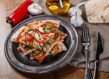 Skivad pizza med höna, zucchinin, aubergine, peppar, ost och champinjoner på plattatappningen royaltyfria bilder