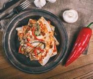 Skivad pizza med höna, zucchinin, aubergine, peppar, ost och champinjoner på plattatappningen royaltyfri bild