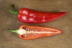 Skivad röd söt peppar som isoleras på träbakgrund Arkivfoto