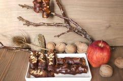 Skivad söt korv med det tokiga och röda äpplet och valnötter på träbräde Arkivbild