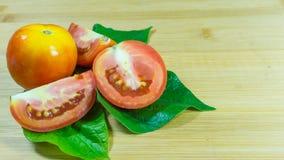 Skivad tomat på träbakgrund arkivbilder