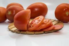 Skivad tomat som ligger på brädet Arkivfoton