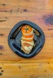 Skivad tomatplatta med skivor av ost, kryddor och olivolja royaltyfria foton