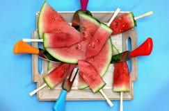 Skivad vattenmelon med pinnar på ett träbräde Fotografering för Bildbyråer