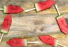 Skivad vattenmelon med pinnar på ett träbräde Royaltyfria Bilder