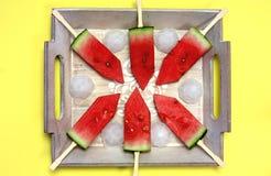 Skivad vattenmelon med pinnar på ett träbräde Arkivfoto
