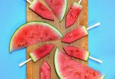Skivad vattenmelon med pinnar på ett träbräde Royaltyfri Bild