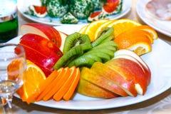 Skivade äpplen, apelsiner på en tabell royaltyfri bild
