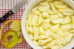 Skivade äpplen med peelen och kniven för en äppelpaj Fotografering för Bildbyråer