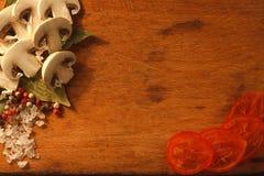 Skivade champignons, körsbärsröda tomater Arkivfoto