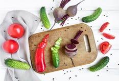Skivade grönsaker för sallad på träskärbräda som omges av grönsaker Lekmanna- lägenhet, bästa sikt arkivfoto